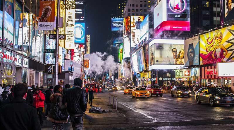 En la imagen aparece la calle de una gran ciudad por la noche, donde cobra protagonismo la presencia de grandes y luminosos carteles publicitarios. El uso de formatos publicitarios capaces de transmitir la propuesta de valor de un despacho debería formar parte de la estrategia comercial de su despacho, siendo el formato video uno de los que aporta más retorno