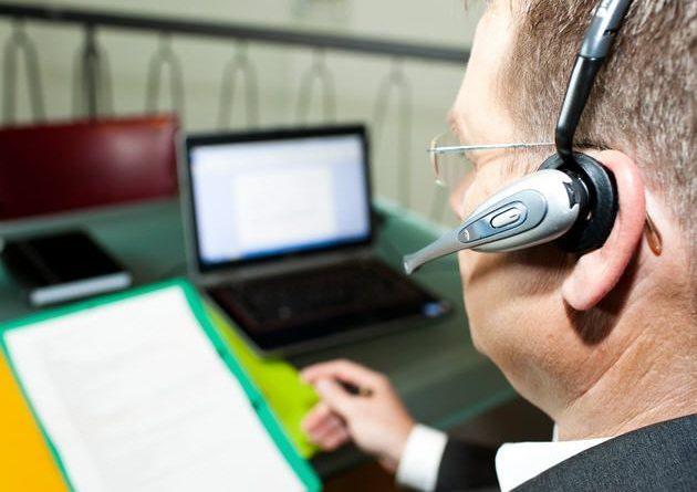 En la imagen aparece un profesional ante su ordenador portátil que está utilizando unos casos con micrófono. Está leyendo un texto y al mismo tiempo su software reconoce su voz para transcribir en el editor del portátil ese texto